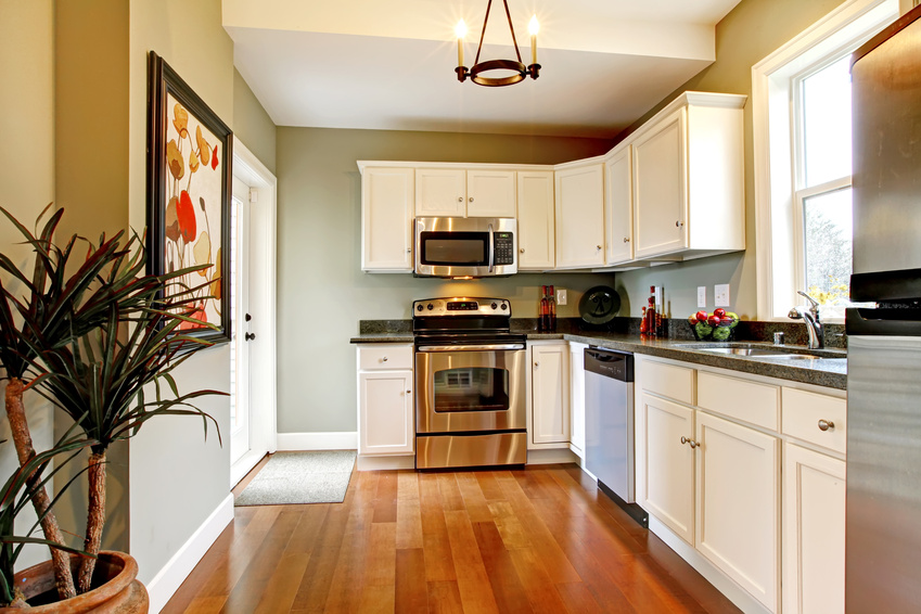 Elegant white and green kitchen with cherry floor.